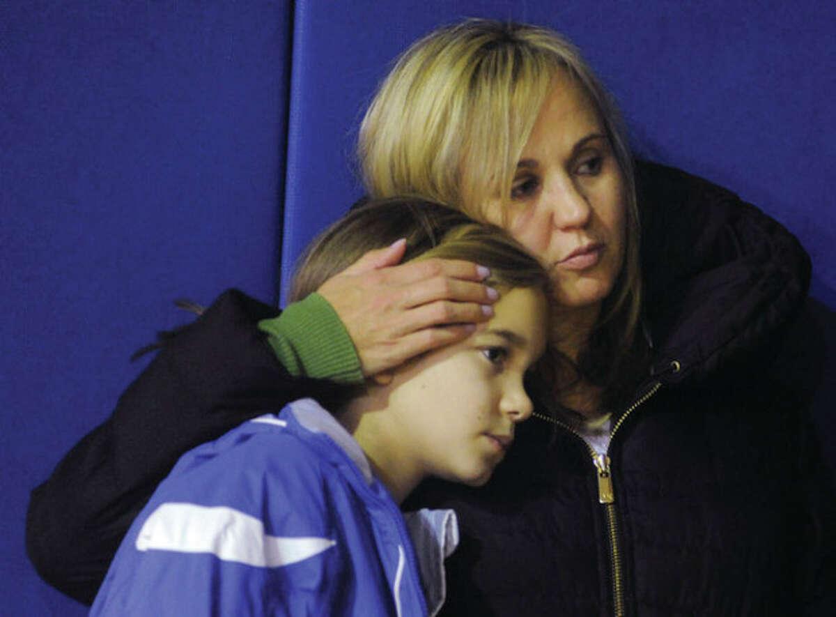 Hour photos / Matthew Vinci Above, Debbie Troy and her daughter Kaitlyn, 11, attend the Narameke School vigil Sunday night to honor the victims of the Sandy Hook Elementary School shootings. Below, Naramake student Breann Memoli attends the vigil.
