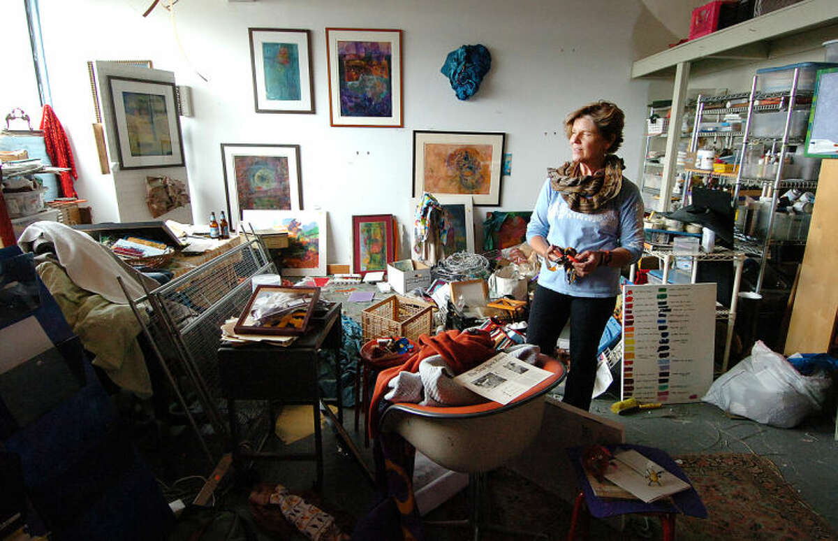 Mixed Media Artist Wendi Ohlson stands in her almost 400-square-foot studio in transition in the Loft Artist Association Studios and Gallery in Stamford.