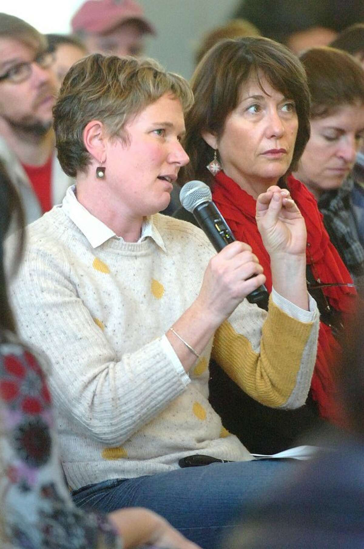 Hour Photo/Alex von Kleydorff. Bridgeport's Anne Watkins asks Jim Himes a question from the audience during a forum hosted by CT Against Gun Violence at Christ and Holy Trinity Church in Westport Monday.