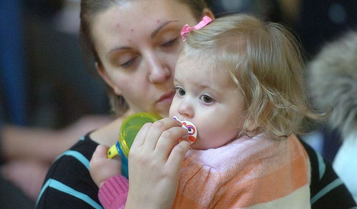 Hour Photo/Alex von Kleydorff. Kyle O'Connor holds onto 16 month old daughter Lilly during a forum hosted by CT Against Gun Violence at Christ and Holy Trinity Church in Westport Monday.