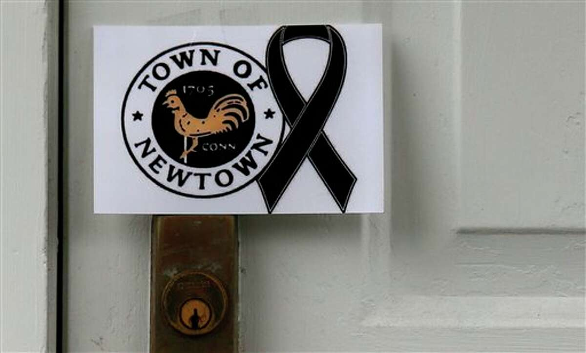 A sign showing the town seal and a black ribbon is posted on the door of an antique colonial home in the historic district near the funeral for six-year-old student shooting victim Jack Pinto in Newtown, Conn., Monday, Dec. 17, 2012. A gunman opened fire at Sandy Hook Elementary School in the town, killing 26 people, including 20 children before killing himself on Friday. (AP Photo/Charles Krupa)