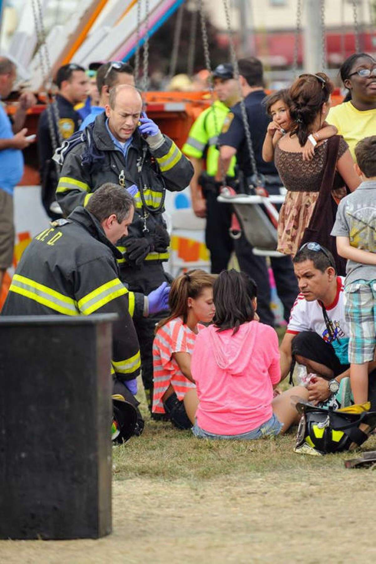 Thirteen children were injured when a festival attraction that swings riders into the air lost power at a community fair in Norwalk, Conn, on Sunday Sept. 8, 2013, but none of the injuries appeared to be life-threatening, authorities said. Most of the children suffered minor injuries and were treated at the Oyster Festival in Norwalk, police said. Norwalk Police Chief Thomas Kulhawik said there were initial reports of serious injuries but preliminary indications are that the injuries were not as severe as first feared. (AP Photo/The Hour Miguel Cruz) MANDATORY CREDIT