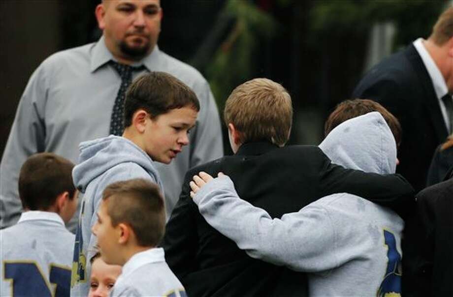 Studens embrace while wearing Newtown school shirts outside the funeral for six-year-old student shooting victim Jack Pinto in Newtown, Conn., Monday, Dec. 17, 2012. A gunman opened fire at Sandy Hook Elementary School in the town on Friday, killing 26 people, including 20 children before killing himself. (AP Photo/Charles Krupa) / 2012 AP