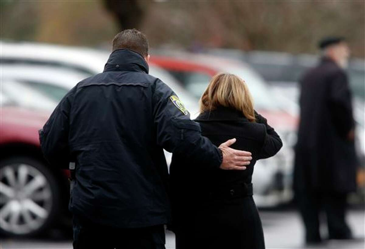 A mourner is comforted by a police officer as she arrives at a funeral service for 6-year-old Noah Pozner, Monday, Dec. 17, 2012, in Fairfield, Conn. Pozner was killed when a gunman walked into Sandy Hook Elementary School in Newtown Friday and opened fire, killing 26 people, including 20 children. (AP Photo/Jason DeCrow)