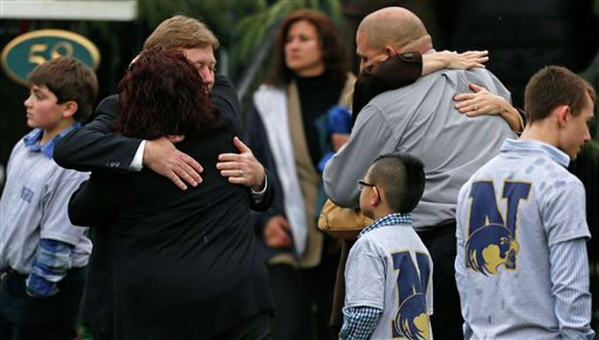 Families embrace while surrounded by children wearing Newtown school shirts outside the funeral for six-year-old shooting victim Jack Pinto in Newtown, Conn., Monday, Dec. 17, 2012. A gunman opened fire at Sandy Hook Elementary School in the town on Friday, killing 26 people, including 20 children before killing himself. (AP Photo/Charles Krupa)