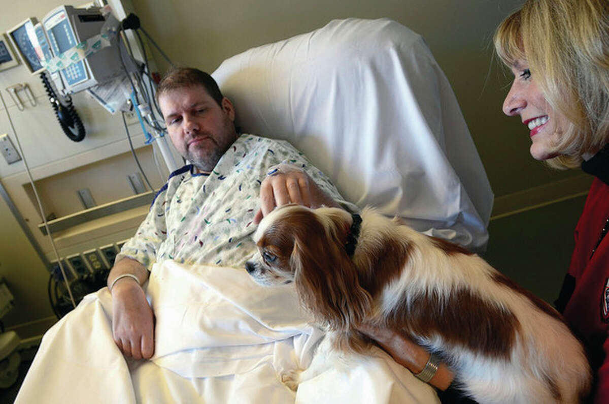 At right, Steven Van Dusen, a patient at CGH Medical Center, pets Cally Lanae, a Cavalier King Charles spaniel owned by Wendy Johnson. Cally is one of 15 dogs participating in the hospital's new