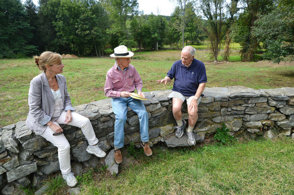 Hour Photo/Alex von Kleydorff. Pat Sesto, Town of Wilton Director of Environmental affairs, Bruce Bebe, President of Wilton Land Conservation Trust's Board of Trustees and Bob Russell, Vice President of Wilton Land Conservation Trust' Board of Trustees, sit on a stone wall that was part of a hitching area for horses and talk about the Keiser property behind them
