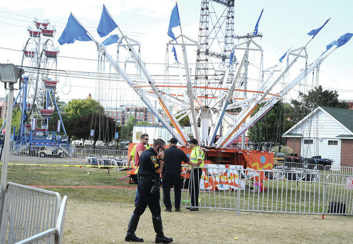 Hour photo/Matthew Vinci Police secure the area of a ride at the Norwalk Oyster Festival Sunday after a ride malfunction caused injuries.
