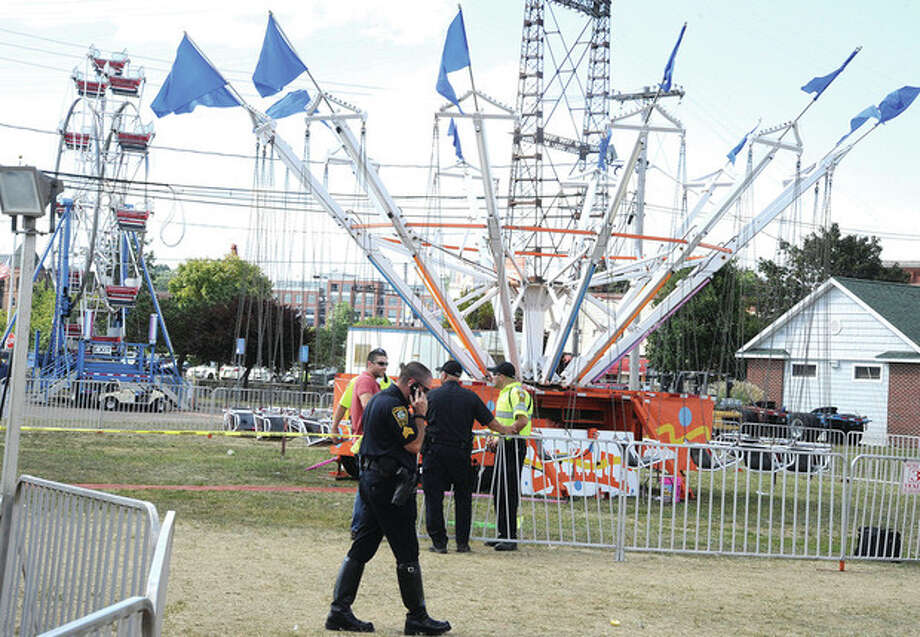 Hour photo/Matthew VinciPolice secure the area of a ride at the Norwalk Oyster Festival Sunday after a ride malfunction caused injuries.