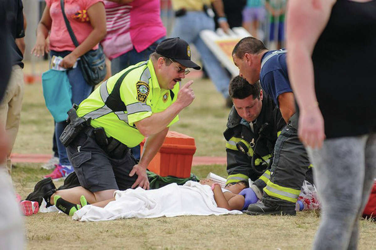 Special to The Hour Miguel Cruz A Norwalk police officer and firefighter tend to one of the injured after a swing ride at the Norwalk Oyster Festival malfuncted Sunday afternoon.