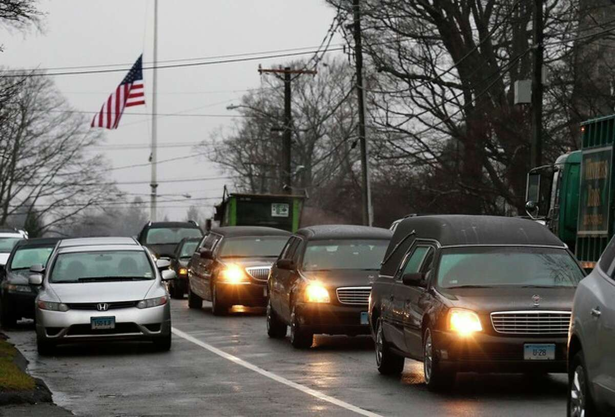 A hearse and family limousines for six-year-old shooting victim Jack Pinto rolls past a flag at half staff as the funeral procession heads through the historic district in Newtown, Conn., Monday, Dec. 17, 2012. A gunman opened fire on Friday at Sandy Hook Elementary School in the town, killing 26 people, including 20 children before killing himself. (AP Photo/Charles Krupa)