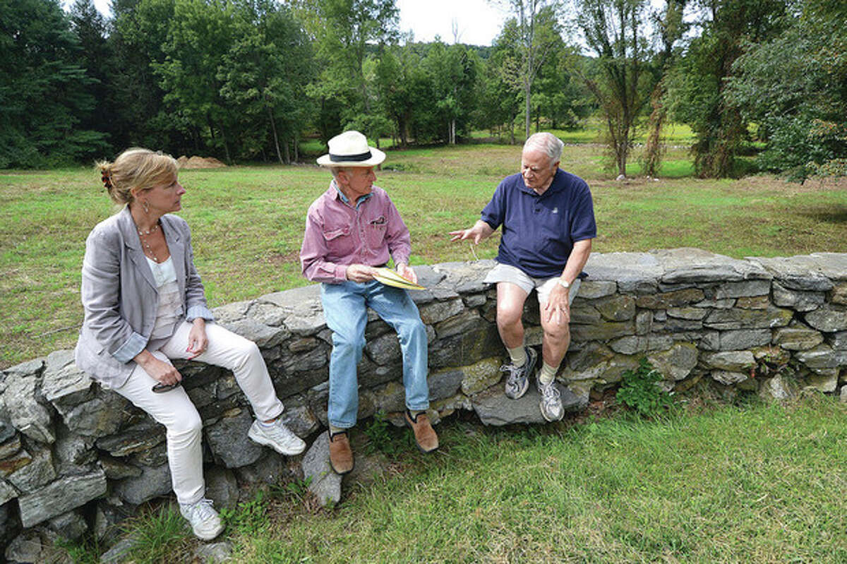 Hour photo / Alex von Kleydorff From left, Pat Sesto, Wilton director of environmental affairs; Bruce Bebe, president of Wilton Land Conservation Trust's Board of Trustees; and Bob Russell, vice president of Wilton Land Conservation Trust' Board of Trustees, sit on a stone wall that was part of a hitching area for horses and talk about the Keiser property stretching behind them.