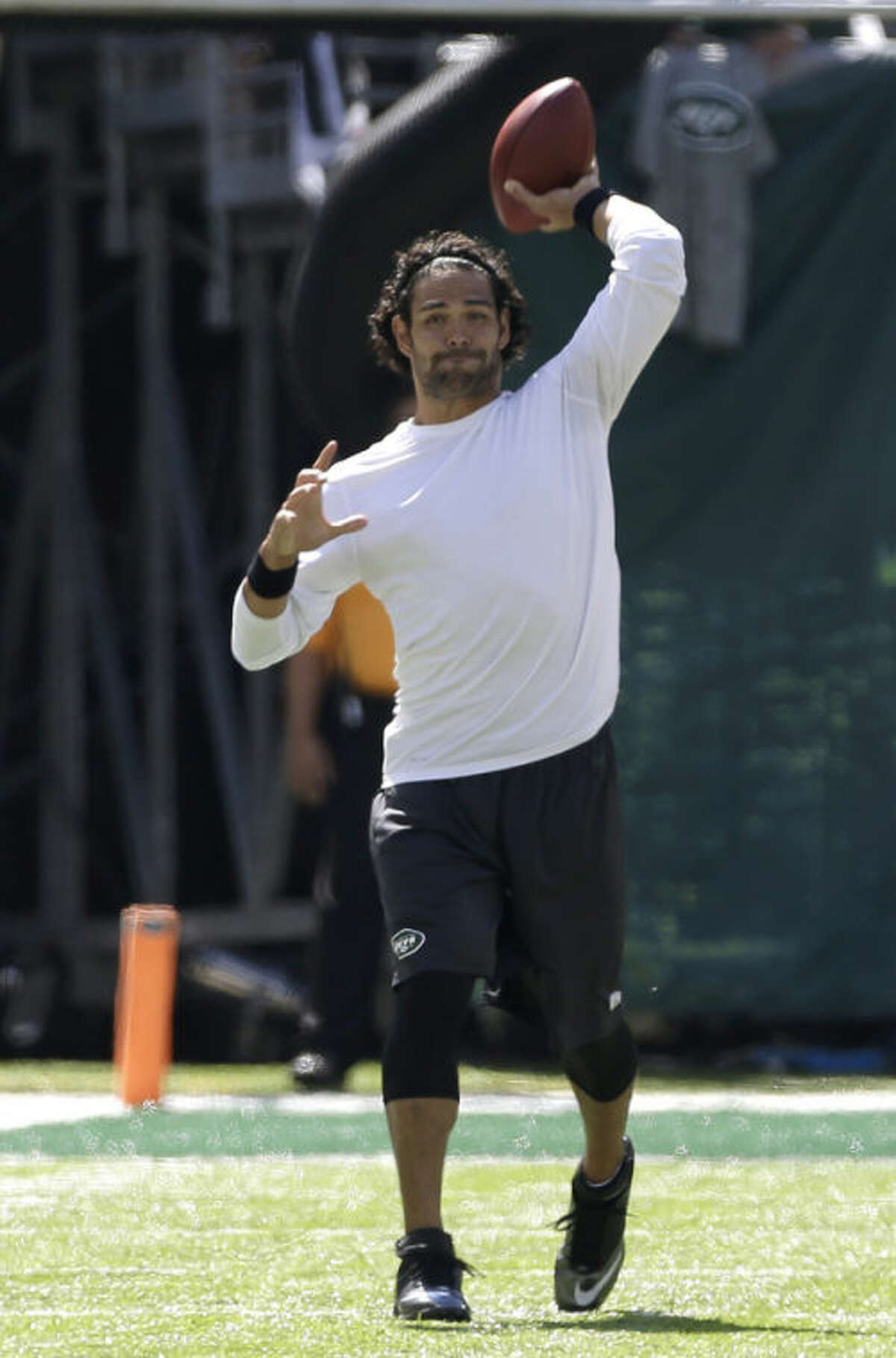 New York Jets quarterback Mark Sanchez throws a left-handed pass before the Jets' NFL football game against the Tampa Bay Buccaneers, Sunday, Sept. 8, 2013, in East Rutherford, N.J. Sanchez was not scheduled to play in the Jets' season-opener because his throwing arm is injured. (AP Photo/Julio Cortez)
