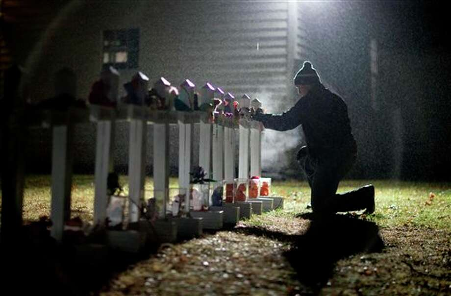 Frank Kulick, adjusts a display of wooden crosses, and a Jewish Star of David, representing the victims of the Sandy Hook Elementary School shooting, on his front lawn, Monday, Dec. 17, 2012, in Newtown, Conn. (AP Photo/David Goldman) / AP