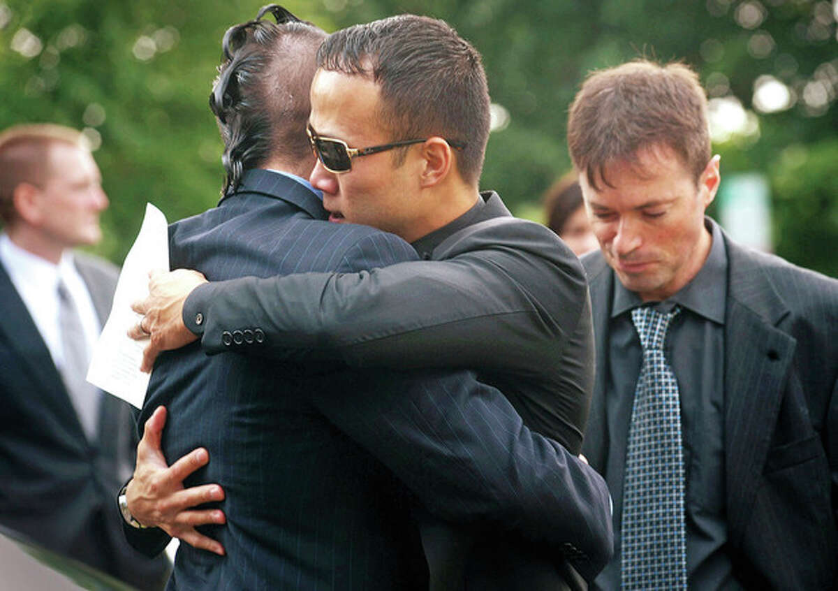 Friends and Catholic University Rugby teammates of the Neil Godleski, Ting Myauo and Peter Glover, embrace following Godleski's funeral Thursday at St. Phillips Church in Norwalk. The 29 year old Norwalk native was shot to death in Washington D.C. Sunday during an apparent robbery attempt. Hour photo / Erik Trautmann