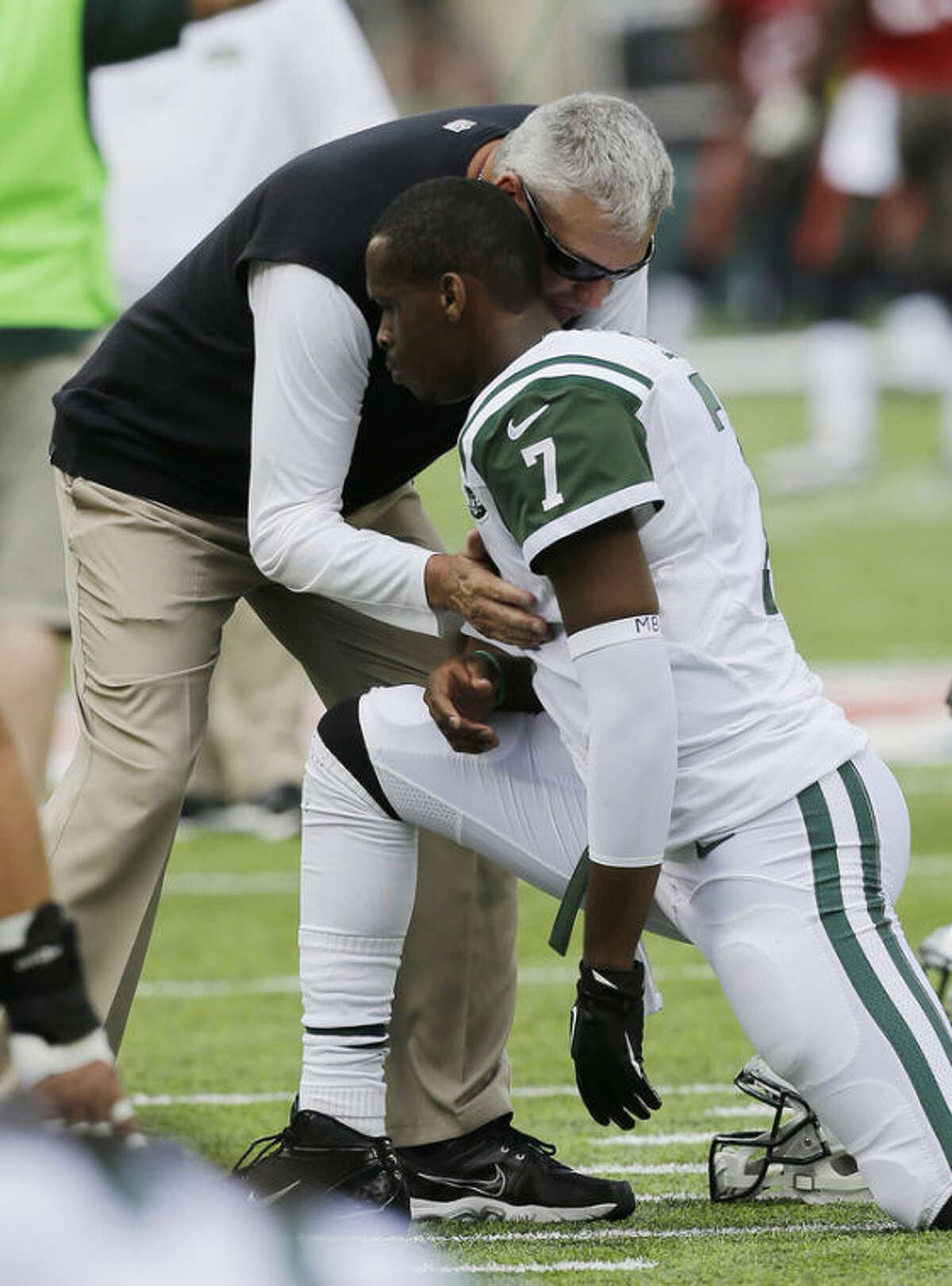 New York Jets coach Rex Ryan, center left, talks to quarterback Geno Smith before an NFL football game against the Tampa Bay Buccaneers, Sunday, Sept. 8, 2013, in East Rutherford, N.J. (AP Photo/Mel Evans)