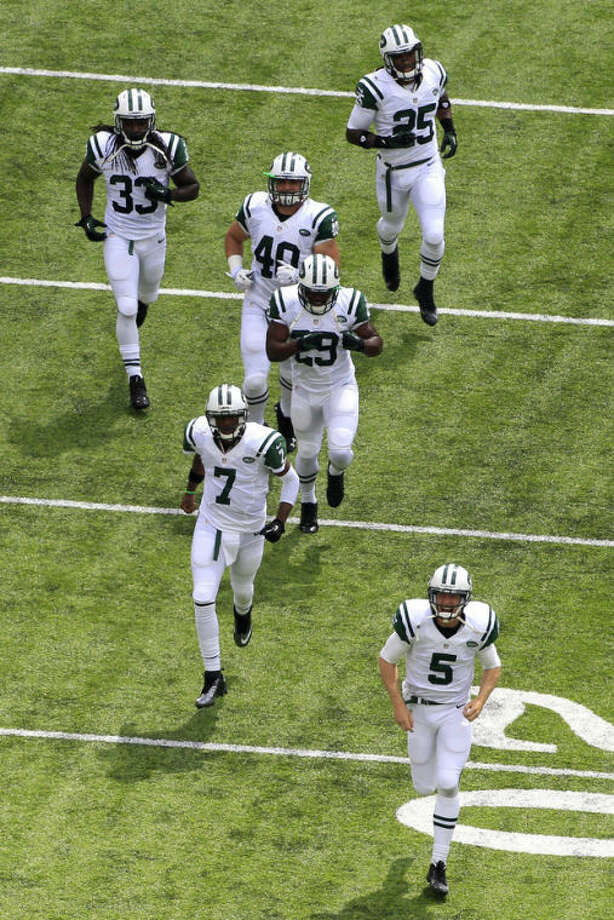 New York Jets quarterbacks Geno Smith (7) and Matt Simms (5) lead the team onto the field before an NFL football game against the Tampa Bay Buccaneers, Sunday, Sept. 8, 2013, in East Rutherford, N.J. (AP Photo/Julio Cortez)