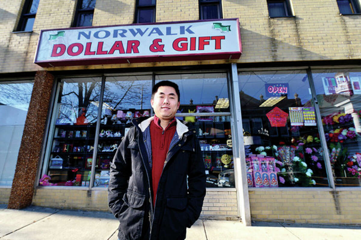 Hour photo / Erik Trautmann Qiwei Chen, owner of Norwalk Dollar & Gift, stands in front of his new store on North Main Street in South Norwalk. Below, shots of some of their merchandise.