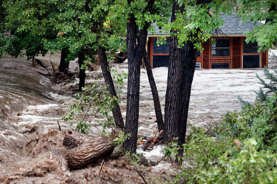 A torrent of water rushes alongside a swamped house following flash flooding near Left Hand Canyon, south of Lyons, Colo., Thursday, Sept 12, 2013. The widespread high waters are keeping search and rescue teams from reaching stranded residents in Lyons and nearby mountain communities as heavy rains hammered northern Colorado. (AP Photo/Brennan Linsley) / AP