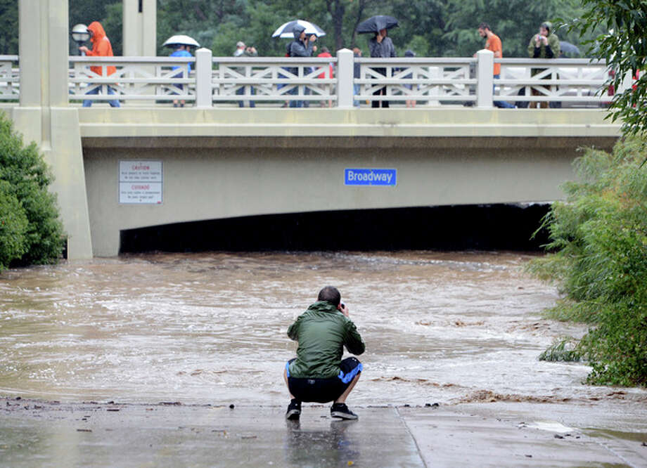 A man photographs the flooding in the underpass at Boulder Creek and Broadway Street in Boulder, Colo. on Thursday, Sept. 12, 2013. Heavy rains and scarring from recent wildfires sent walls of water crashing down mountainsides early Thursday in Colorado, cutting off mountain towns. Boulder County was hit hardest, but flooding was reported all along the Front Range, from Colorado Springs to north of Fort Collins. (AP Photo/The Daily Camera, Cliff Grassmick NO SALES / The Daily Camera