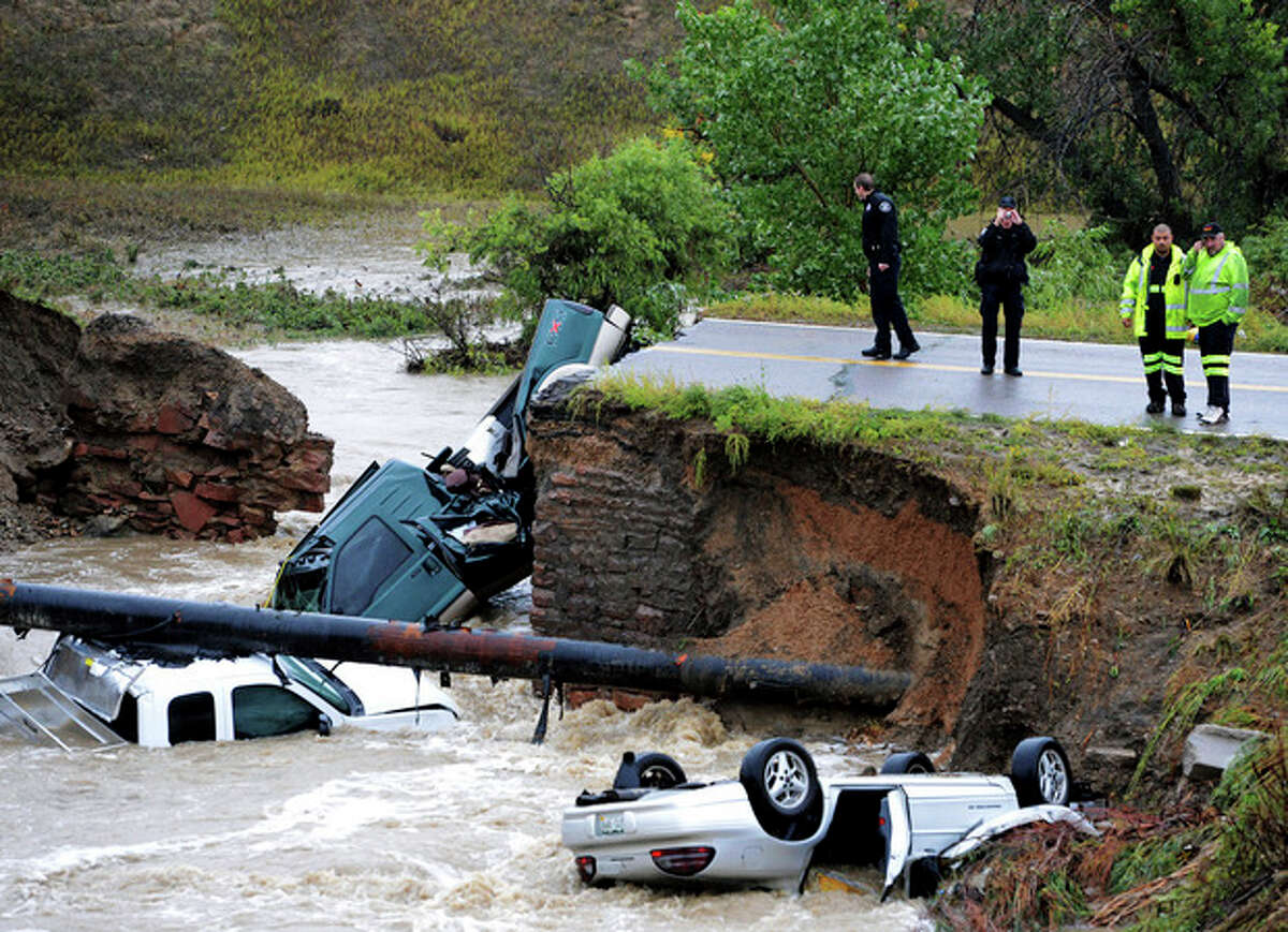 Officials investigate the scene of a road collapse at Highway 287 and Dillon at the Broomfield/Lafayette border, Colo., that sent three vehicles into the water after flash flooding on Thursday, Sept. 12, 2013. The National Weather Service has warned of an