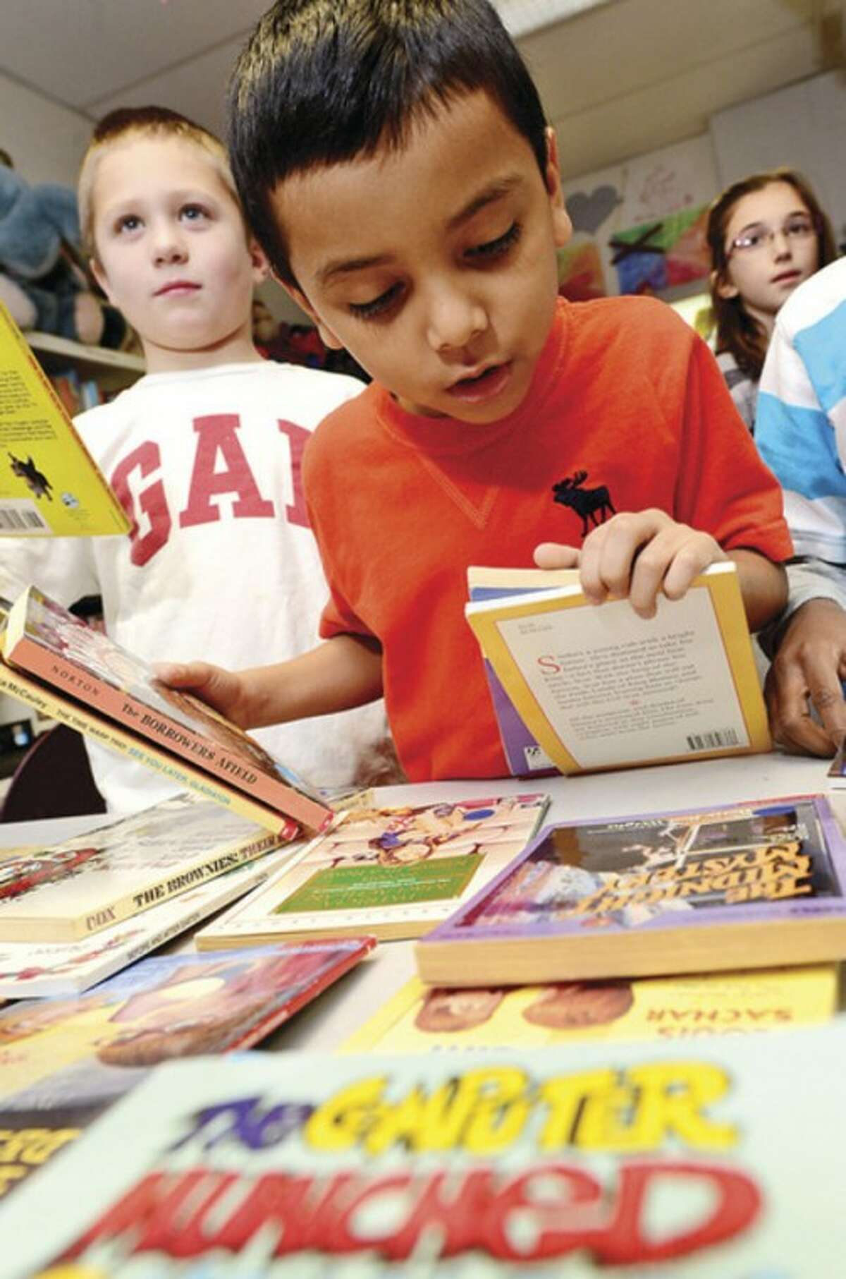 3rd graders Carlos Reyes and Matthew Claps pick out books during free book distribution at Fox Run School Thursday. The collaboration between United Way and Norwalk Read Thursday morning gave away nearly 2000 books ands plans to give away 12,000 this year. Hour photo / Erik Trautmann