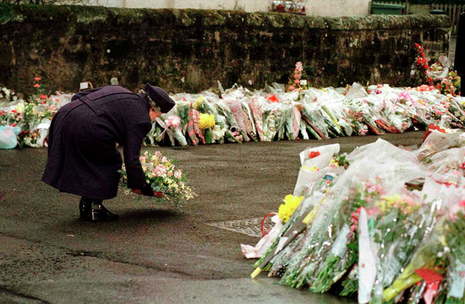 FILE - In this March 17, 1996 file photo, Britain's Queen Elizabeth places a floral bouquet with hundreds of others in front of Dunblane Primary School. In March 1996, a 43-year-old man named Thomas Hamilton walked into a primary school in this central Scotland town of 8,000 people and shot to death 16 kindergarten-age children and their teacher with four legally held handguns. In the weeks that followed, people in the town formed the Snowdrop campaign - named for the first flower of spring - to press for a ban on handguns. Within weeks, it had collected 750,000 signatures. By the next year, the ban had become law. (AP Photo/Ian Waldie, Pool-File) / POOL REUTERS