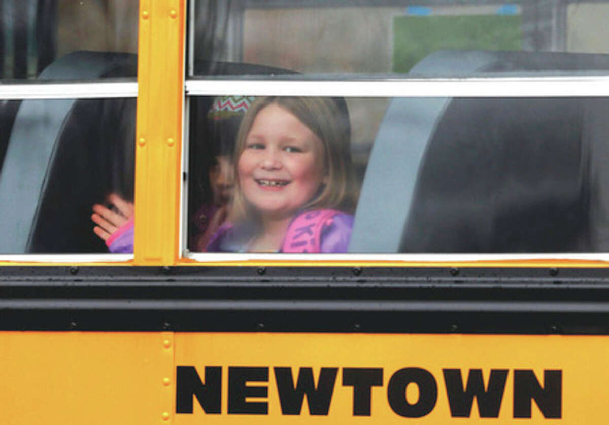AP photo / Jason DeCrow A young girl waves as her school bus pulls into Hawley School Tuesday in Newtown. Classes resumed Tuesday for Newtown, except those at Sandy Hook.