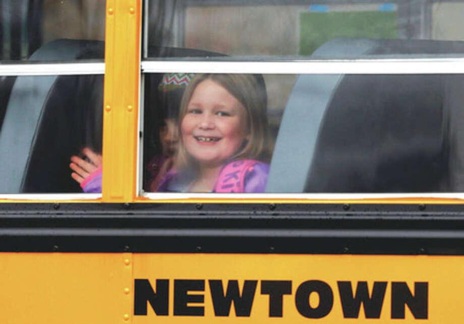 AP photo / Jason DeCrowA young girl waves as her school bus pulls into Hawley School Tuesday in Newtown. Classes resumed Tuesday for Newtown, except those at Sandy Hook. / FR103966 AP