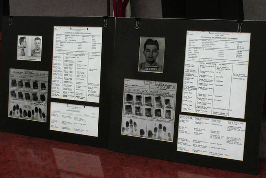 "This photo from Tuesday, Dec. 18, 2012, shows a display of prison records for Richard Hickock, left, and Perry Smith, used at a news conference in Lansing, Kan. The two men were executed for the 1959 multiple murders that inspired Truman Capote's book, ""In Cold Blood,"" and their remains have been exhumed and reburied so that authorities could collect DNA samples as possible evidence linking them to Florida killings. (AP Photo/John Hanna) / AP"