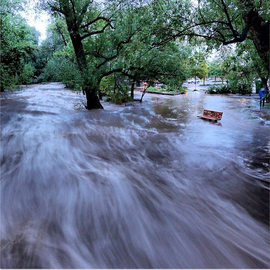In this image made with a slow shutter speed which blurred the rushing water, flood waters course through a small park in Boulder, Colo., Thursday morning, Sept. 12, 2013. Heavy rains and scarring from recent wildfires sent walls of water crashing down mountainsides in the area. (AP Photo/Jud Valeski) / @jvaleski