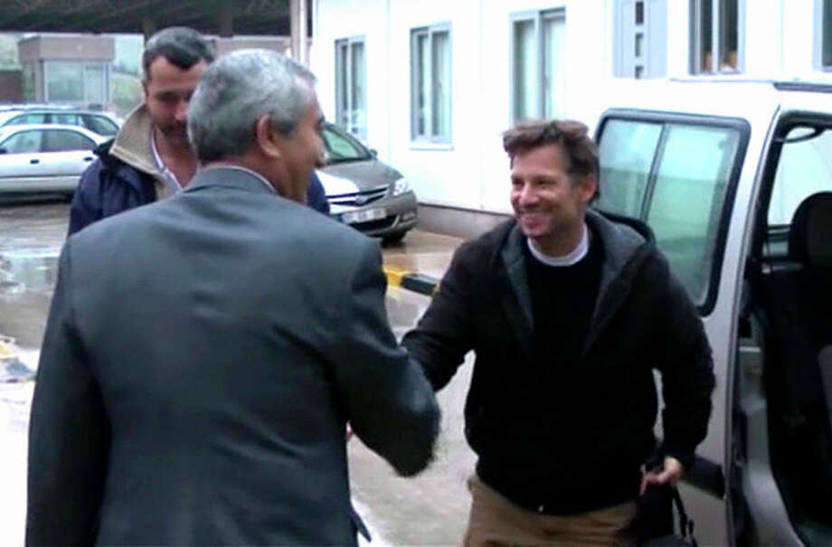 "In this image made from video, NBC chief foreign correspondent Richard Engel, right, shakes hands with an unidentified person after crossing back into Turkey, after they were freed unharmed following a firefight at a checkpoint after five days of captivity inside Syria, in Cilvegozu, Turkey, Tuesday, Dec. 18, 2012. Engel told the Turkish news agency Anadolu that he and his colleagues are ""very happy to be out"" and they are ""very tired."" (AP Photo/Anadolu via AP TV) TURKEY OUT, TV OUT / Anadolu via AP TV"