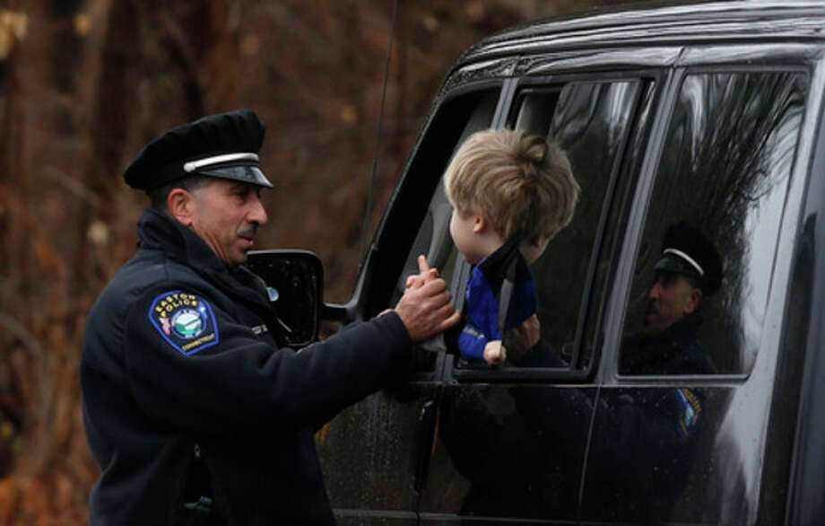 Easton police officer J. Sollazzo clasps hands with a young student returning to Hawley School, Tuesday, Dec. 18, 2012, in Newtown, Conn. Classes resume Tuesday for Newtown schools except those at Sandy Hook. Buses ferrying students to schools were festooned with large green and white ribbons on the front grills, the colors of Sandy Hook. At Newtown High School, students in sweatshirts and jackets, many wearing headphones, betrayed mixed emotions. Adam Lanza walked into Sandy Hook Elementary School in Newtown, Friday and opened fire, killing 26 people, including 20 children, before killing himself.(AP Photo/Jason DeCrow) / FR103966 AP