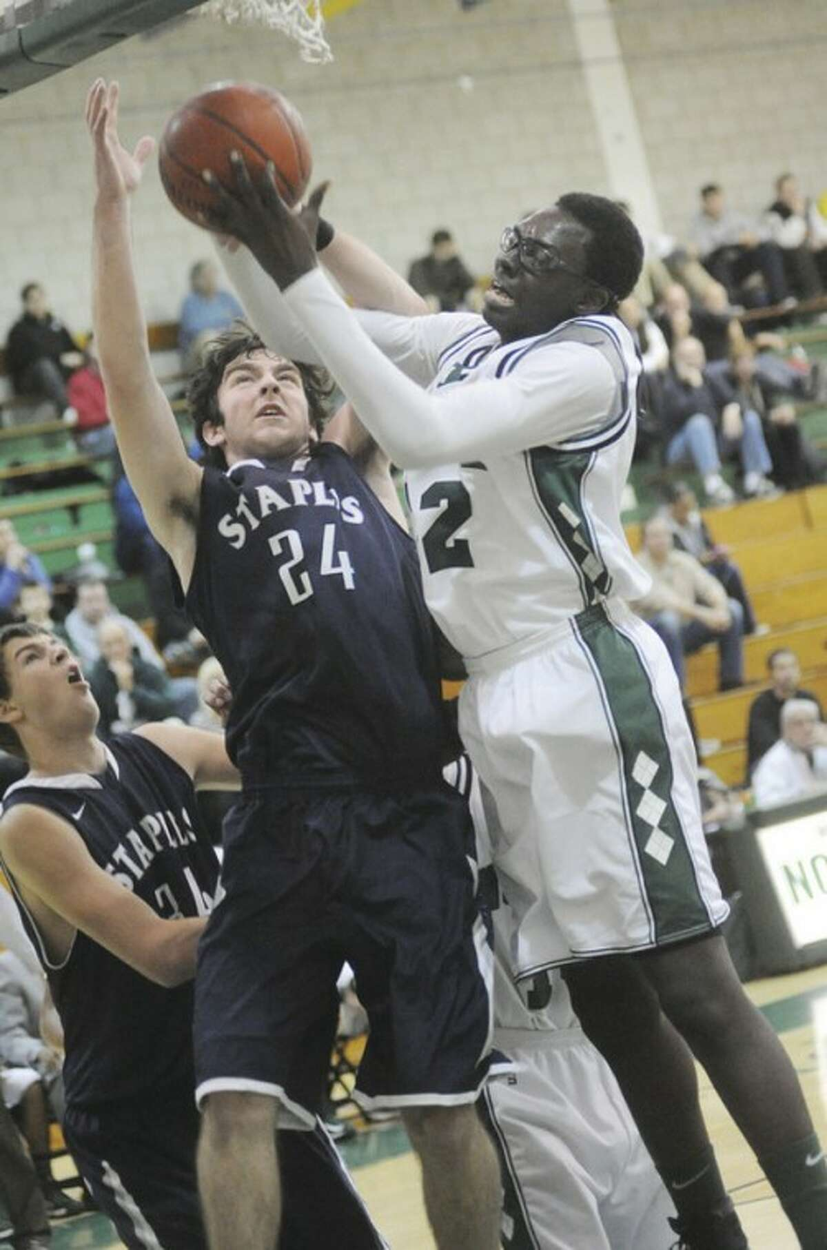 Hour photo/Matthew Vinci Norwalk's Roy Kane Jr., right, snags a rebound away from Ross Whelan of Staples during Tuesday night's game at Norwalk's Scarso gym. The Bears were forced into overtime before finally defeating the Wreckers, 84-75.
