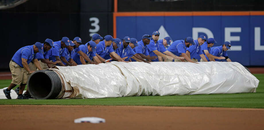 Groundskeepers roll the tarp onto the outfield as rain headed into the area after the first inning of a baseball game between the Washington Nationals and the New York Mets Thursday, Sept. 12, 2013, in New York. (AP Photo/Kathy Willens) / AP