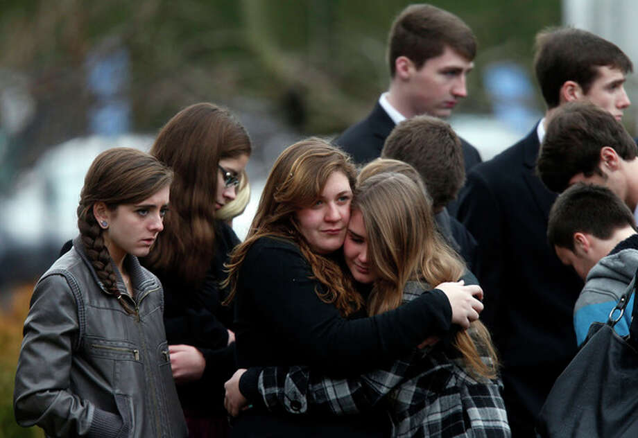 Mourners comfort one another as they leave a funeral service for 6-year-old Noah Pozner, Monday, Dec. 17, 2012, in Fairfield, Conn. Pozner was killed when a gunman walked into Sandy Hook Elementary School in Newtown Friday and opened fire, killing 26 people, including 20 children. (AP Photo/Jason DeCrow) / FR103966 AP