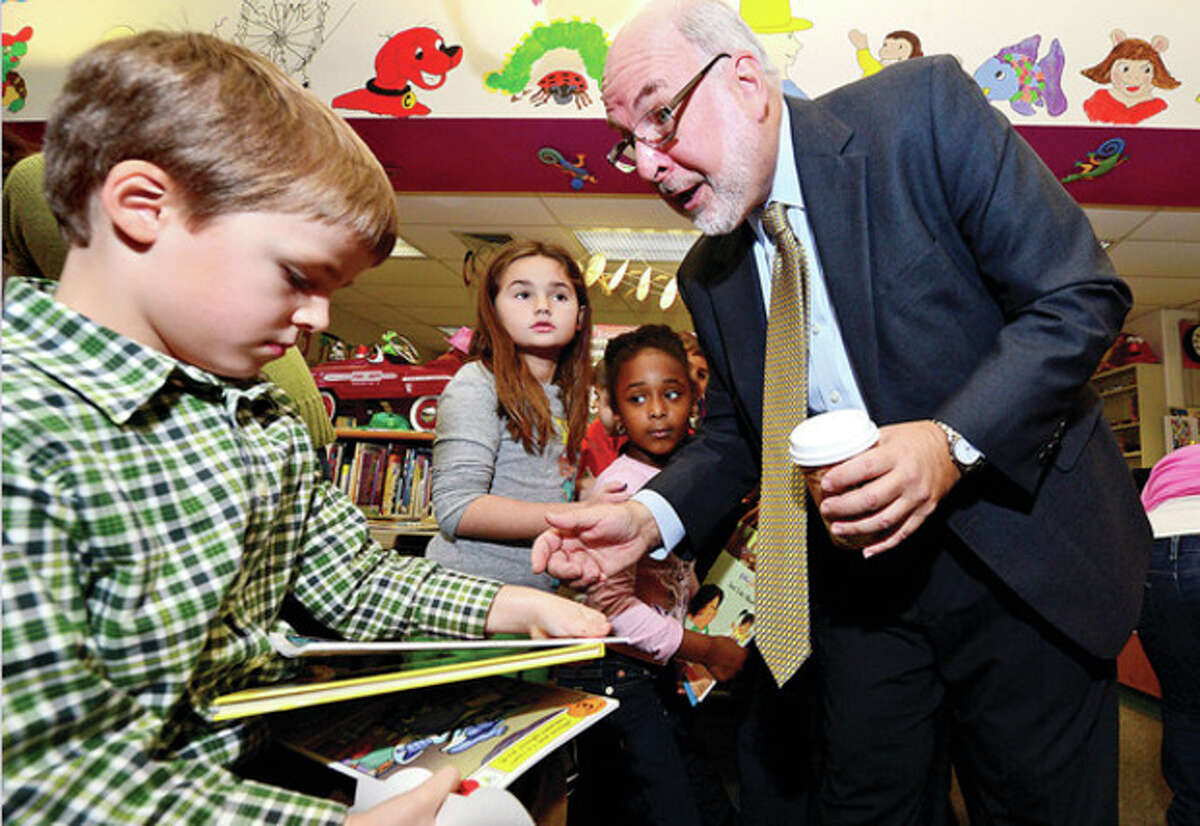Stephen Bentkover of The United Way chats with kindergartner James BIckle during a free book distribution at Fox Run School Thursday. The collaboration between United Way and Norwalk Read gave away nearly 2000 books Thursday morning. Hour photo / Erik Trautmann
