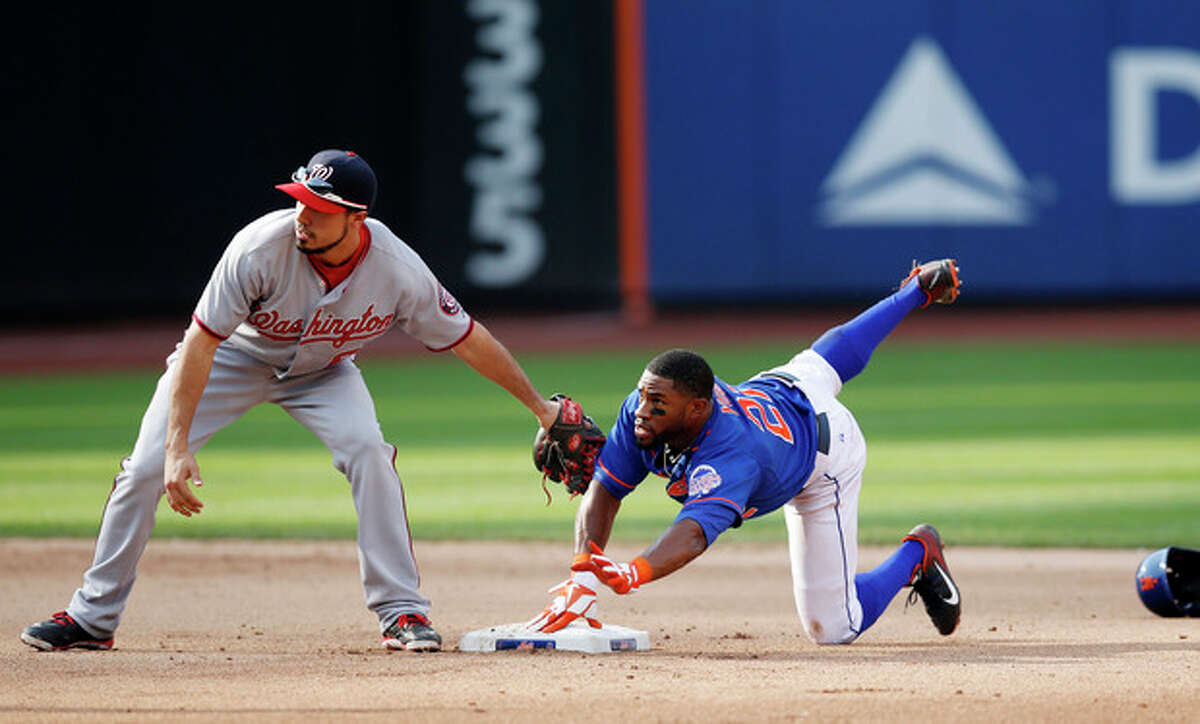 Washington Nationals second baseman Anthony Rendon, left, and New York Mets' Eric Young, right, look for the umpire's call after Young stole second in the seventh inning of a baseball game on Thursday, Sept. 12, 2013, in New York. The Nationals won 7-2. (AP Photo/Kathy Willens)