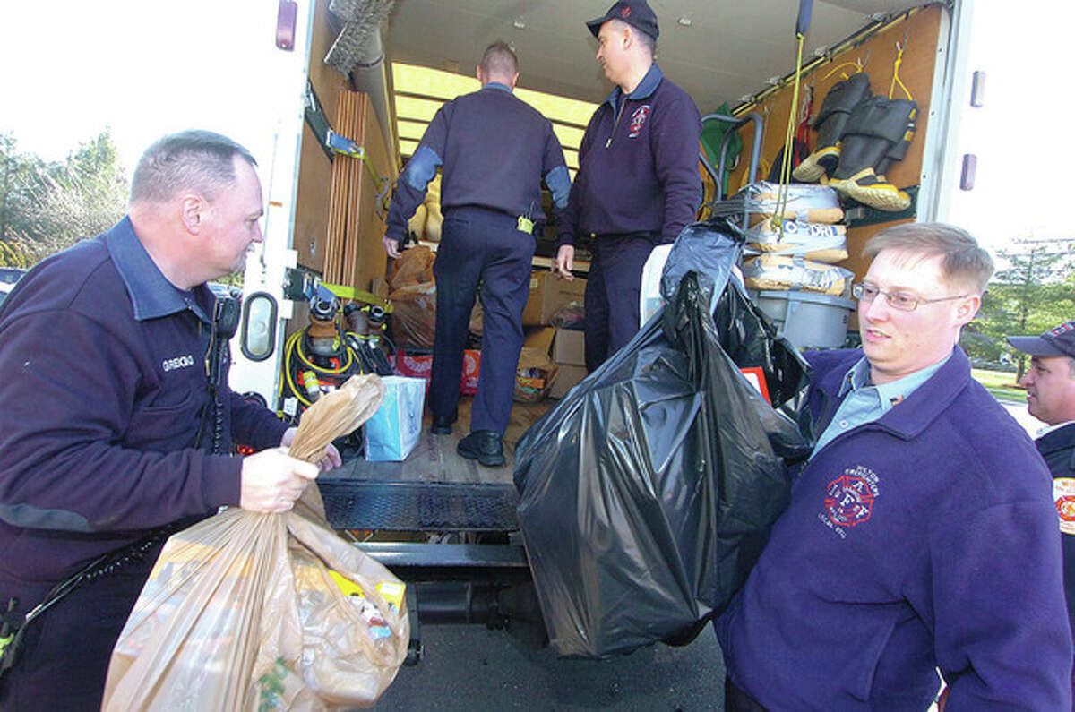 Hour Photo/Alex von Kleydorff. Wilton Firefighters Gregg Kitik and Brian Elliott help to unload a box truck and add to the more than 500 toys they have colledted for the Toys for Tots program.