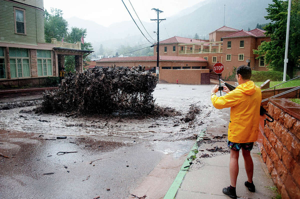 John Shada, of Manitou Springs, Colo., takes a photo of flood water as it shoots out of a sewer on Canon Avenue on Thursday, Sept. 12, 2013, in Manitou Springs, Colo. Flash flooding in Colorado has cut off access to towns, closed the University of Colorado in Boulder and left at least three people dead. (AP Photo/The Colorado Springs Gazette, Michael Ciaglo)
