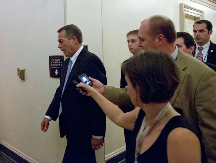 Speaker John Boehner of Ohio, center, departs, with reporters nearby after a House Republicans meeting on Capitol Hill, Thursday, Dec. 20, 2012 in Washington. Confronted with a revolt among the rank and file, House Republicans abruptly put off a vote Thursday night on legislation allowing tax rates to rise for households earning $1 million and up.(AP Photo/Alex Brandon) / AP