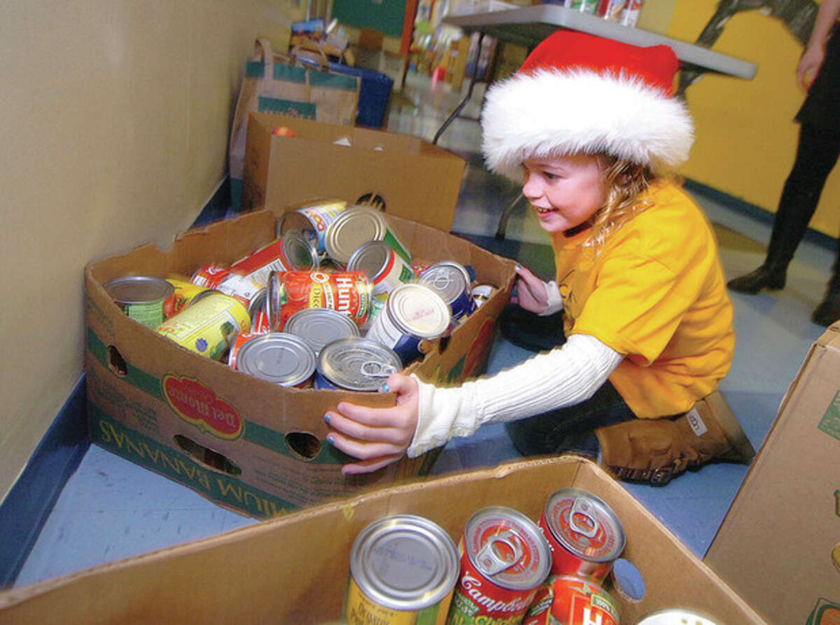 Hour Photo/Alex von Kleydorff. Aubrey Bransher moves some boxes of canned goods that students use for payment to buy stamps at The Columbus Magnet School Post Office