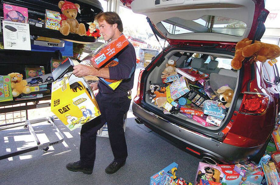 Hour photo / Alex von KleydorffWilton Firefighter Glen Johnson moves toys from the Wilton Motors showroom into a truck for the Marines Toys for Tots program. / 2012 The Hour Newspapers/Alex von Kleydorff