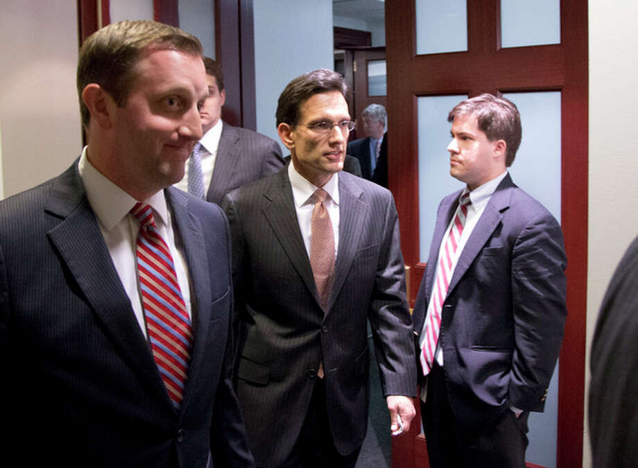 Majority Leader Eric Cantor from Virginia, center, departs after a House Republicans meeting on Capitol Hill, Thursday, Dec. 20, 2012 in Washington. Confronted with a revolt among the rank and file, House Republicans abruptly put off a vote Thursday night on legislation allowing tax rates to rise for households earning $1 million and up.(AP Photo/Alex Brandon) / AP