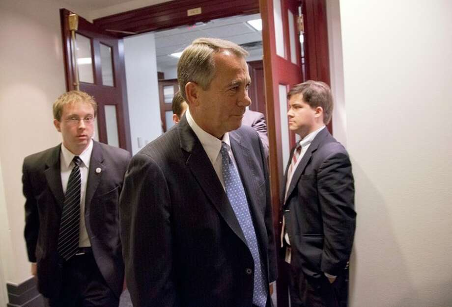 Speaker John Boehner of Ohio, center, departs after a House Republicans meeting on Capitol Hill, Thursday, Dec. 20, 2012 in Washington. Confronted with a revolt among the rank and file, House Republicans abruptly put off a vote Thursday night on legislation allowing tax rates to rise for households earning $1 million and up.(AP Photo/Alex Brandon) / AP