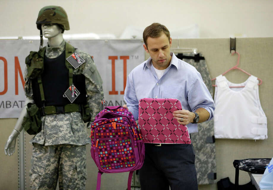 Rick Brand, Chief Operating Officer of Amendment II, holds a children's backpack, left, and anti-ballistic insert at the company's manufacturing facility in Salt Lake City, Wednesday, Dec. 19, 2012. Anxious parents reeling in the wake the Connecticut school shooting are fueling sales of armored backpacks for children emblazoned with Disney and Avengers logos, as firearms enthusiasts stock up on assault rifles nationwide amid fears of imminent gun control measures. At Amendment II, sales of children's backpacks and armored inserts are up 300 percent. (AP Photo/Rick Bowmer) / AP