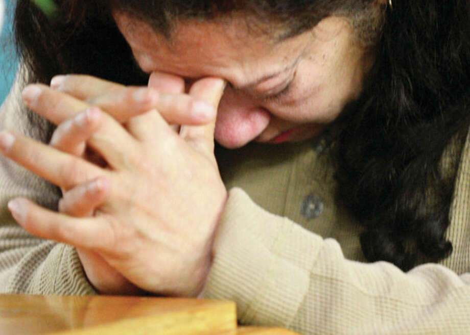 A woman bows her head in prayer while local officials hold a brief ceremony with a moment of silence in honoring the victims of the Sandy Hook shooting which claimed the livees of 26 people including 20 children.Hour photo / Erik Trautmann / (C)2012, The Hour Newspapers, all rights reserved
