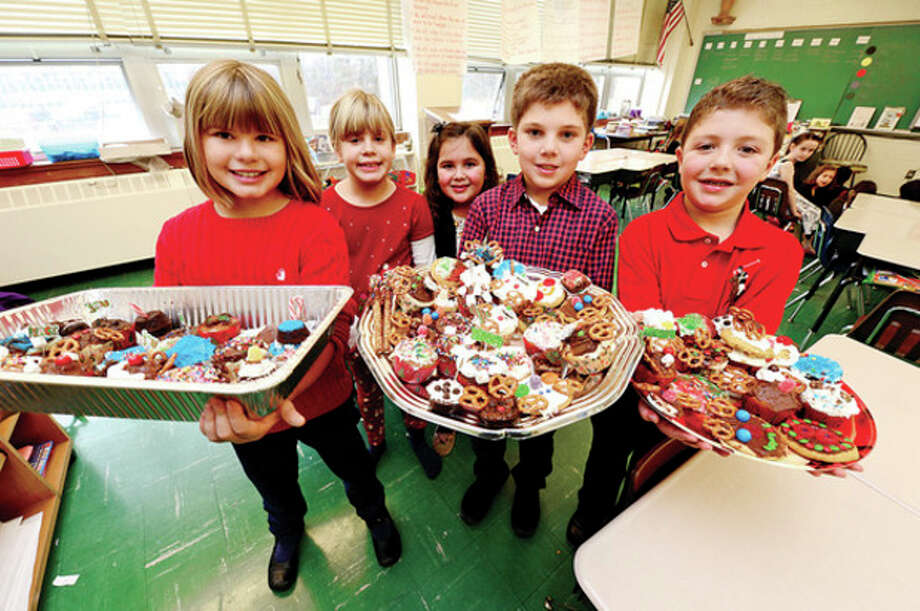 All Saints Catholic School first graders in Kristin Maloney's class including Kaitlyn Geigmetter, Mia Geigmetter, Molly Goldstein, Mark Armatowski and Joseph Cirifalco prepare goodies to benefit Person-to-Person. / (C)2012, The Hour Newspapers, all rights reserved