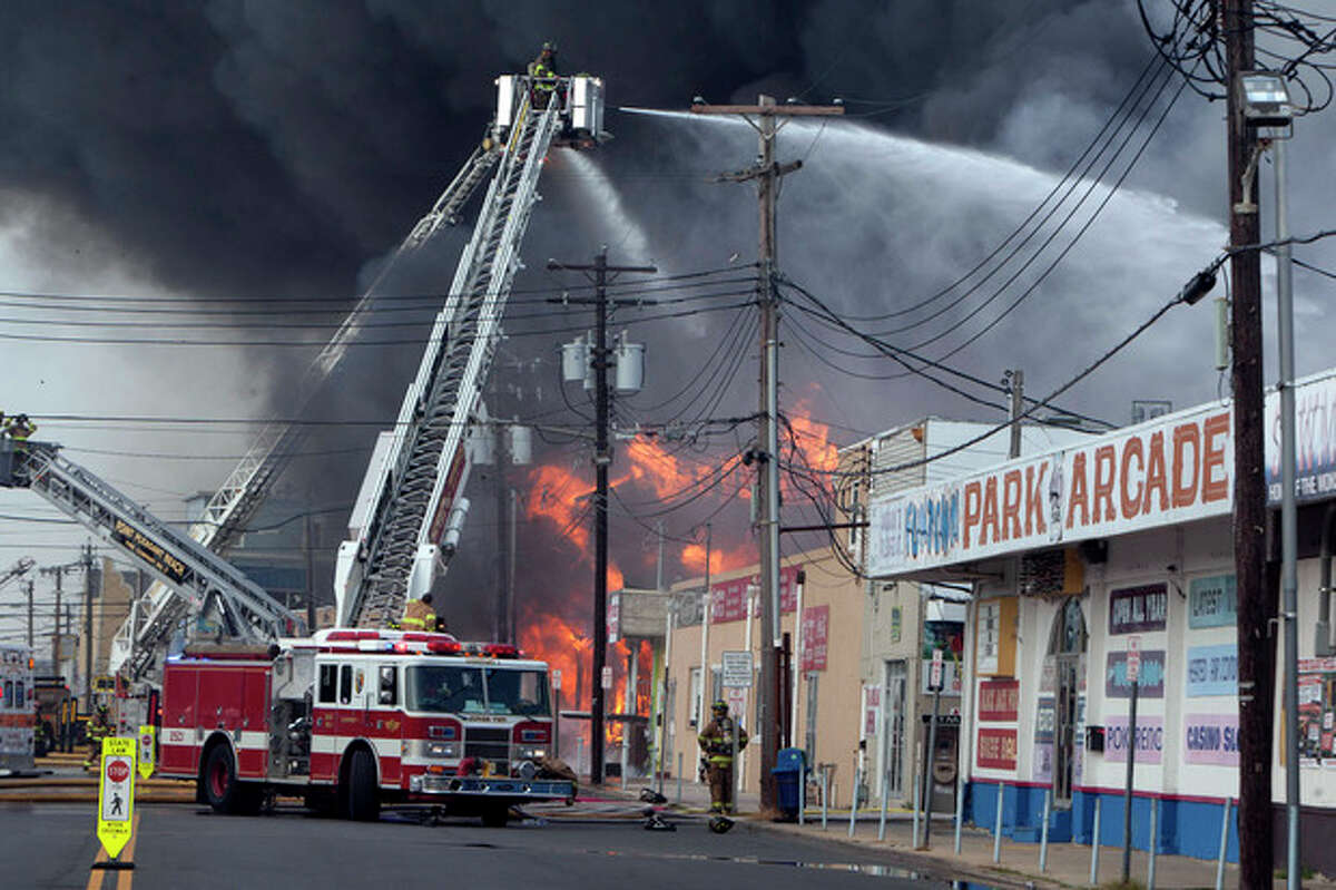 Firefighters battle a fire on the Seaside Heights, N.J. boardwalk Thursday, Sept. 12, 2013. The fire started in the vicinity of an ice cream shop and burned several blocks of boardwalk and businesses in a town that was still rebuilding from damage caused by Superstorm Sandy. (AP Photo/The Asbury Park Press, Bob Bielk) NO SALES