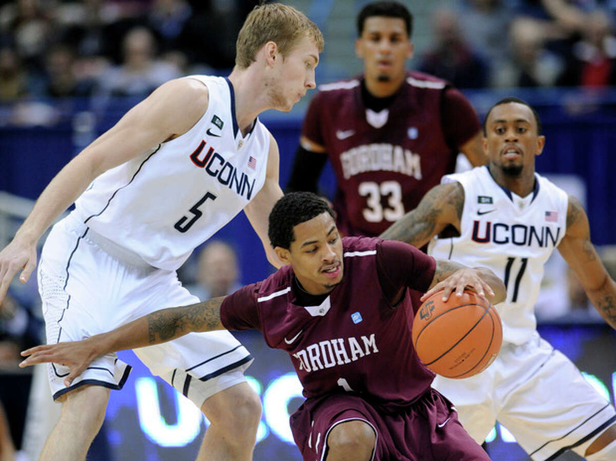 Fordham's Branden Frazier, center, is guarded by Connecticut's Niels Giffey, left, and Ryan Boatright during the first half of an NCAA college basketball game in Hartford, Conn., Friday, Dec. 21, 2012. (AP Photo/Fred Beckham)